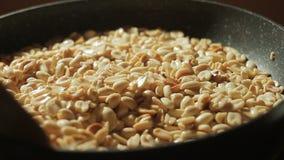 De gepelde pinda's zijn gebraden in een pan Hand met lepel het bewegen noten stock videobeelden