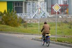 De gepensioneerde in een hoed berijdt een fiets op de hoofdweg stock foto's