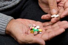 De gepensioneerde houdt heel wat gekleurde pillen in oude handen Pijnlijke oude dag Gezondheidszorg van oudere mensen Stock Afbeeldingen