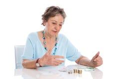 De gepensioneerde telt haar inkomen - oudere die vrouw op witte rug wordt geïsoleerd stock fotografie