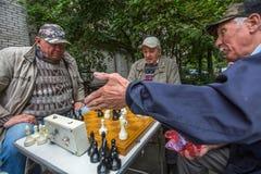 De gepensioneerden spelen schaak in de binnenplaats van een flatgebouw Stock Fotografie