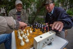 De gepensioneerden spelen schaak in de binnenplaats van een flatgebouw Royalty-vrije Stock Foto's