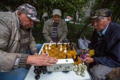 De gepensioneerden spelen schaak in de binnenplaats van een flatgebouw Stock Foto