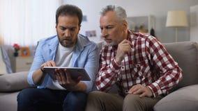 De gepensioneerdenpapa op middelbare leeftijd van het zoonsonderwijs om bankwezen app op tablet te gebruiken, technologie?n stock video