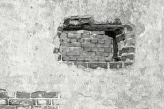 De gepleisterde muur van grijze kleur met een gat Stock Fotografie
