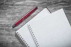 De geregelde pen van de notitieboekjesballpoint op het houten concept van het raadsbureau royalty-vrije stock afbeelding