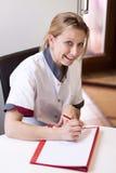 De geriatrische verpleegster maakt nota's over een patiënt Stock Afbeelding