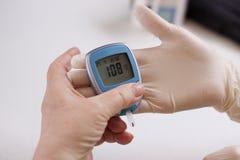 De geriatrische verpleegster meet het glucoseniveau Royalty-vrije Stock Foto's