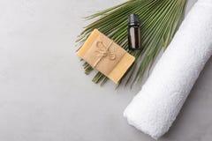 De gerolde witte zuivere van de katoenen etherische olie badstofhanddoek in donker de zeeppalmblad van flessen artisanaal Marseil stock afbeeldingen