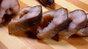 De gerookte paling wordt gesneden in gedeelten stock video