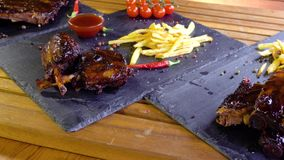 De geroosterde bbq ribben van het varkensvleesvlees op steenplaat stock videobeelden