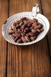 De geroosterde bonen van de cacaochocolade in oude geweven emailzeef, streven na Stock Fotografie