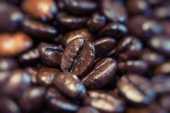 De geroosterde bruine koffiebonen, kunnen als achtergrond worden gebruikt Royalty-vrije Stock Afbeeldingen
