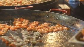 De geroosterde garnalen zijn gebraden in een grote pan, bereidt de chef-kok de voorbereide garnalen voor Gebraden zeevruchten op  stock footage