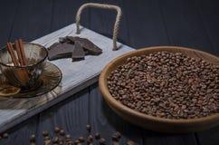 De geroosterde geurige korrels van zwarte koffie liggen in een bruine houten plaat die zich op een zwarte houten lijst en naast h royalty-vrije stock foto