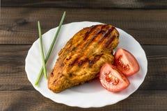 De geroosterde gezonde kippenborst diende met tomaat en vers bieslook op witte plaat op houten lijst Royalty-vrije Stock Afbeeldingen
