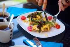 De geroosterde groene asperge met scrumbled eieren op de gehele tarwetoost eet door een jonge mens royalty-vrije stock afbeeldingen