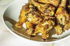 De geroosterde kippentrommelstokken braadden knapperig gemarineerd met honing wordt gediend in een vlakke witte schotel op een wi Royalty-vrije Stock Foto