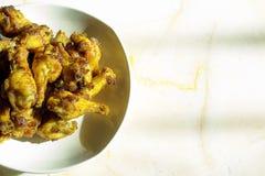 De geroosterde kippentrommelstokken braadden knapperig gemarineerd met honing wordt gediend in een vlakke witte schotel op een wi Stock Afbeeldingen
