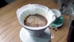 De geroosterde koffie in filter wordt gegoten door warm water stock videobeelden