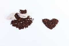 De geroosterde koffiebonen in een vod doet, geroosterde koffiebonen op een wh in zakken Royalty-vrije Stock Afbeeldingen