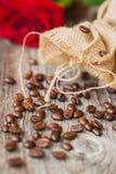De geroosterde koffiebonen op een bruine houten achtergrond, ruwe ruwweg geweven jute en rood namen, grunge textuur toe selectief Stock Foto