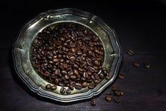 De geroosterde koffiebonen op een oud verzilverd tafelgerei op een donker bruin streven na Stock Foto