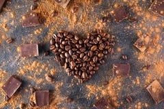 De geroosterde koffiebonen in de vorm van een hart op de donkere steenachtergrond met verdrijven cacao, stukken van chocolade en  Royalty-vrije Stock Afbeeldingen