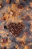 De geroosterde koffiebonen in de vorm van een hart op de donkere steenachtergrond met verdrijven cacao, stukken van chocolade en  Stock Fotografie