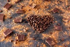 De geroosterde koffiebonen in de vorm van een hart op de donkere steenachtergrond met verdrijven cacao, stukken van chocolade en  Royalty-vrije Stock Afbeelding