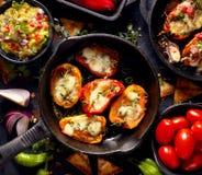 De geroosterde paprika'spopcornpannen vulden met kaas en kruiden, mengelings heerlijke voorgerechten op een zwarte achtergrond stock foto