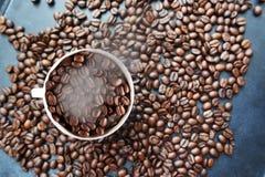 """De geroosterde textuur van koffiebonen met koffiebonen verspreidde zich op donkere achtergrond en witte kop†""""hoogste mening Stock Afbeelding"""