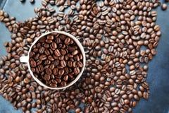 """De geroosterde textuur van koffiebonen met koffiebonen verspreidde zich op donkere achtergrond en witte kop†""""hoogste mening Royalty-vrije Stock Foto"""