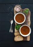 De geroosterde tomatensoep met vers basilicum, de kruiden en het brood in uitstekend metaal werpen op houten raad over zwarte ach royalty-vrije stock foto's