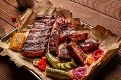 De geroosterde varkensvleesribben dienden met geroosterd graan, salat, bbq saus, zoute peper en komkommer op perkamentdocument op Stock Afbeeldingen