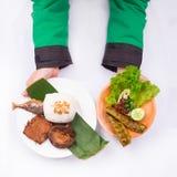 De geroosterde vissen met gebraden tempeh, petai, komkommer, sla, leunca, braadden sjalot, en witte rijst met hand Stock Fotografie