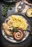 De geroosterde worst met Fijngestampte Aardappels en de ingelegde kool in metaalplaat met bestek dienden op donkere rustieke lijs Royalty-vrije Stock Afbeeldingen