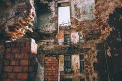 De geruïneerde bouw, oude ruïnes van baksteen huisvest gebroken door oorlog, aardbeving of andere natuurramp Vernieling de bouwco stock afbeeldingen
