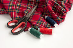 De geruit Schots wollen stofstof, de schaar en de naaiende draden Royalty-vrije Stock Fotografie