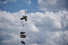 De gescheurde oude tennisschoenen hangen op de draad stock fotografie