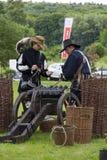 De geschiedenisfans kleedden zich aangezien de militairen van de de 17de eeuwhuurling van hem laden Royalty-vrije Stock Afbeeldingen