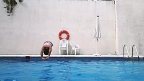 De geschikte Kaukasische mens duikt hoofd eerst in de pool stock footage