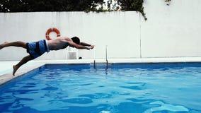 De geschikte Kaukasische mens duikt hoofd eerst in de pool stock videobeelden