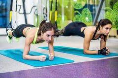 De geschikte meisjes die in gymnastiek plank doen oefenen voor rug uit royalty-vrije stock foto's