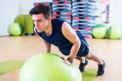 De geschikte mens die met baltraining uit uitoefenen bewapent Oefening opleidingstriceps en bicepsen die duw UPS doen stock afbeeldingen