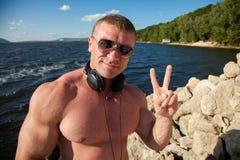 De geschikte slanke atleet met oortelefoons stelt aan camera Stock Foto's