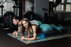 De geschikte sportieve man en de vrouw die plankkern doen oefenen opleiding terug en van de het conceptengymnastiek van persspier royalty-vrije stock foto