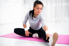 De geschikte vrouw die aerobicsgymnastiek het uitrekken doen zich oefent haar been en thuis terug naar opwarming op yogamat uit Stock Fotografie