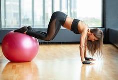 De geschikte vrouw die in gymnastiek abs doen exrcise op fitball stock foto's