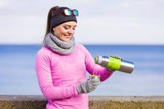 De geschikte vrouw in het koude dag opwarmen drinkt thee stock fotografie
